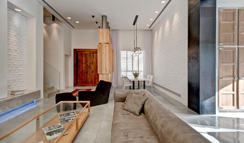 קרן מימון, ריצוף בטון מוחלק, קירות לבנים ותאורה כללית הנשענת ברובה (צילום: עודד סמדר)