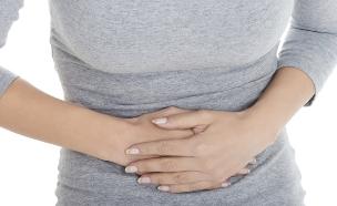 אישה מחזיקה את הבטן (צילום: אימג'בנק / Thinkstock)