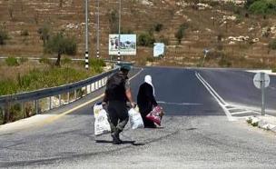 """לוחם מגב עוזר לפלסטינית (צילום: מתוך עמוד הפייסבוק """"חיילים מצייצים"""")"""