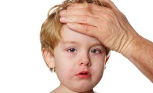 יד גברית על מצח של ילד בלונדיני בוכה וחולה (צילום: istockphoto)