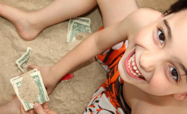 ילד בחוף הים מחזיק כסף (צילום: אימג'בנק / Thinkstock)