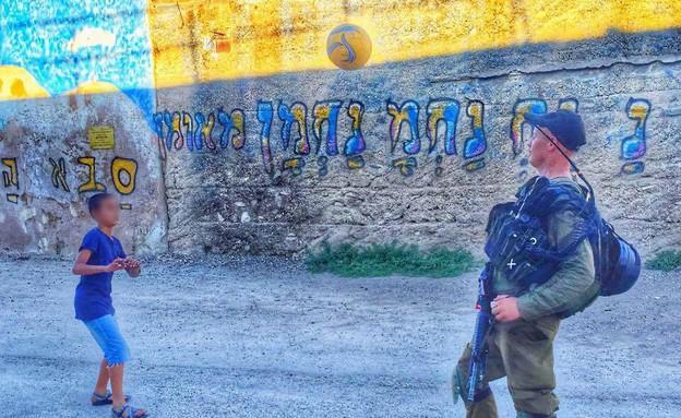 חייל כפיר משחק עם ילד (צילום: מתוך דף הפייסבוק של ויצה סיבנקוב)