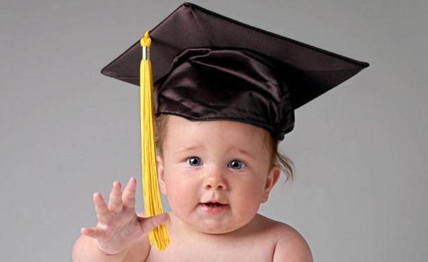תינוק בחיתול יושב על רצפה עם כובע אקדמאי וידיים מו (צילום: jupiter images)