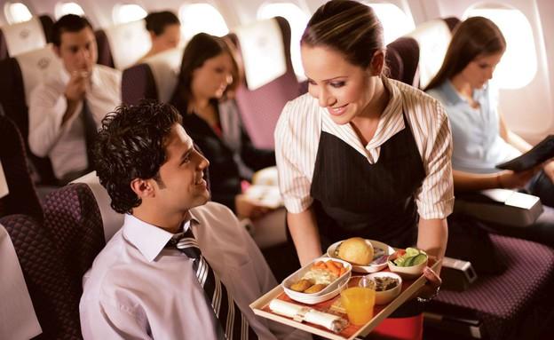 בתוך מטוס - דיילת מגישה לנוסע אוכל (צילום: Royal Jordanian)