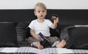 תינוק יושב על ספה ומחזיק כרטיסי אשראי (אילוסטרציה: Snejana_1974, Thinkstock)