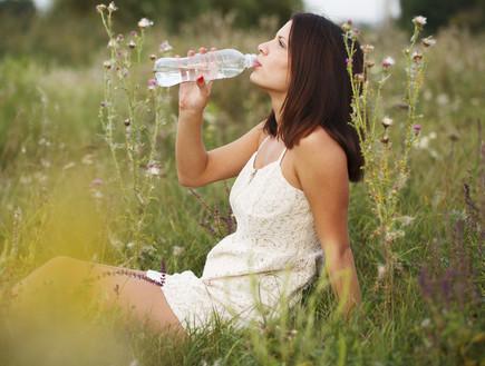 אישה בשדה שותה מבקבוק מים
