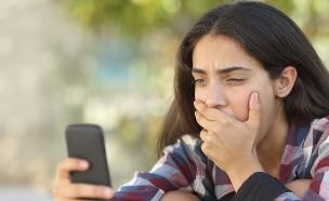 נערה מסתכלת על סמארטפון מודאגת (צילום: Thinkstock)