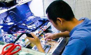 טכנאי מתקן סמארטפונים (צילום: Mitch Altman, Flickr)