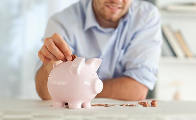 איש שם כסף בחזיר קופת חיסכון (צילום: Wavebreak Media LTD, Thinkstock)
