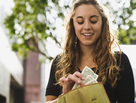 אשה מסתכלת על ארנק מלא בכסף