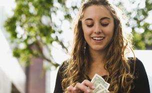 אשה מסתכלת על ארנק מלא בכסף (אילוסטרציה: Brand X Pictures, Thinkstock)