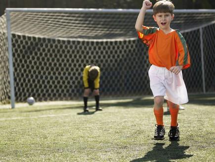 ילד משחק כדורגל