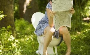 אישה בשירותים קוראת עיתון (צילום: אימג'בנק / Thinkstock)