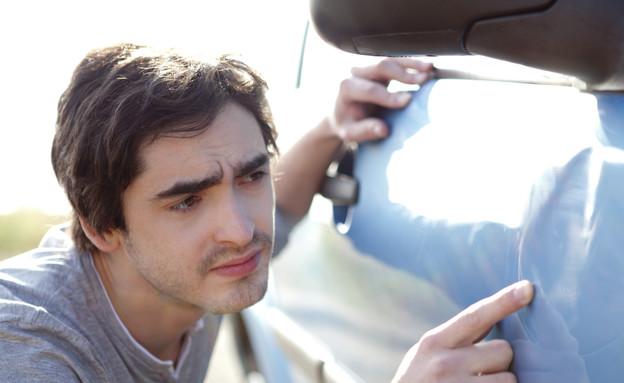 גבר צעיר מסתכל על שריטות על מכונית (אילוסטרציה: pp76, Thinkstock)
