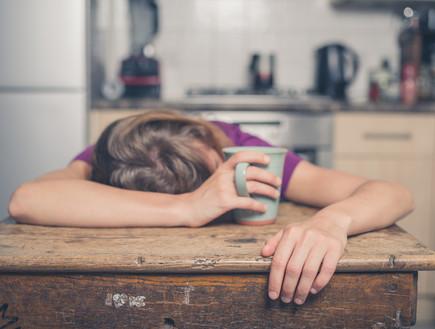 אישה עייפה מרוחה על השולחן עם כוס קפה ביד (צילום: LoloStock / Shutterstock)