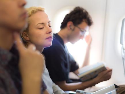 אישה ישנה במטוס