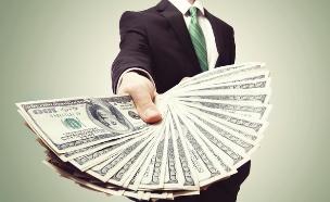 איש עסקים מחזיק חבילת דולרים (אילוסטרציה: Shutterstock)