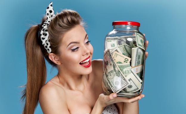 אישה מסתכלת על צנצנת של כסף (אילוסטרציה: Shutterstock)
