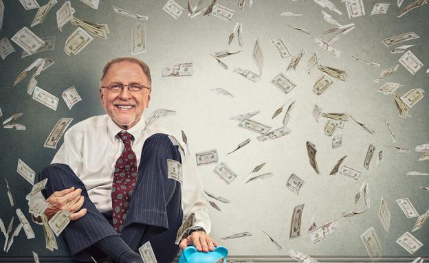 גבר יושב ליד קופת חיסכון תחת גשם של כסף (אילוסטרציה: Shutterstock)