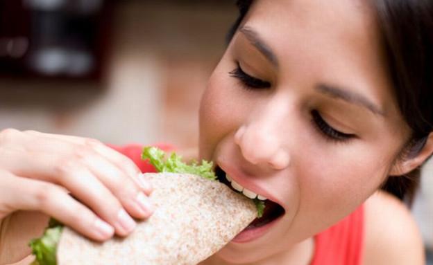 בחורה אוכלת פיתה מגולגלת עם חסה (צילום: Aldo Murillo, Istock)