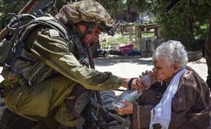 חייל משקה אישה מבוגרת (צילום: צילום מסך מתוך www.israelvideonetwork.com)