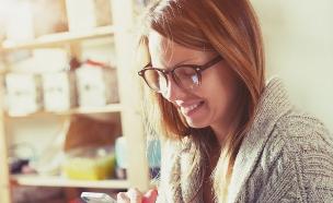 אישה מסתכלת בסמארטפון (צילום: Shutterstock)