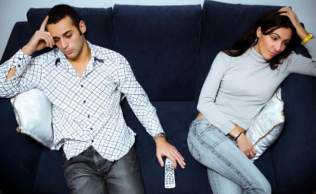 זוג מיואש על ספה מחזיקים את הראש וביניהם שלט (צילום: istockphoto)