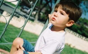 ילד עומד ליד גדר (צילום: istockphoto)