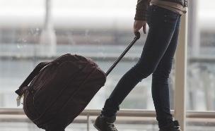 אישה עם טרולי בשדה תעופה (צילום: Pavel Ilyukhin, Shutterstock)