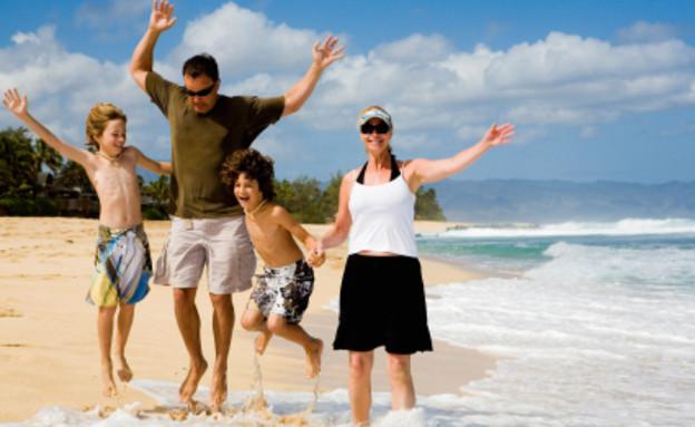 אבא אמא ושני ילדים בים, קופצים (צילום: istockphoto)