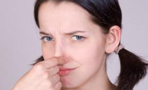 אישה סותמת את האף (צילום: Milan Vasicek, Istock)