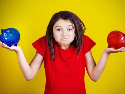 ילדה מבולבלת מחזיקה שתי קופות חיסכון