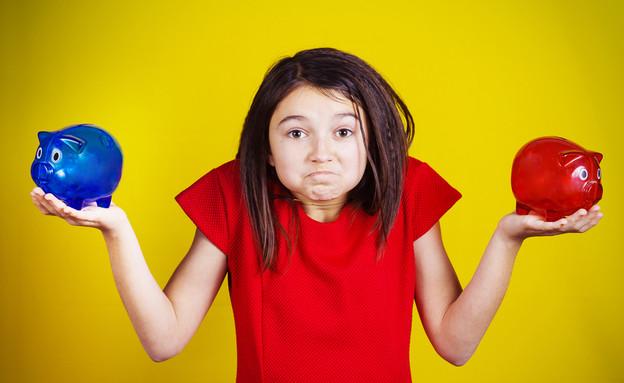 ילדה מבולבלת מחזיקה שתי קופות חיסכון (אילוסטרציה: Shutterstock)