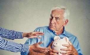 גבר מבוגר מנסה להגן על קופת החיסכון שלו (אילוסטרציה: Shutterstock)