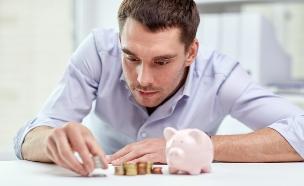 איש עסקים סופר מטבעות ליד קופת חיסכון (אילוסטרציה: Shutterstock)