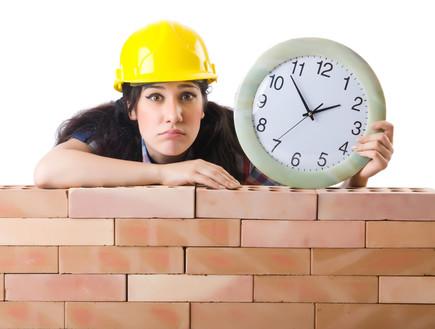 פועלת בניין מחזיקה שעון (אילוסטרציה: Shutterstock)