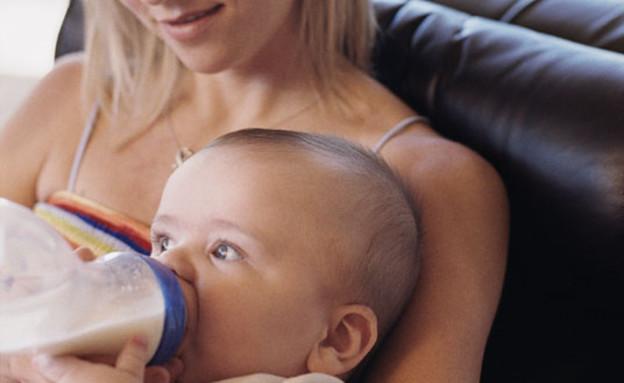 אישה מאכילה תינוק בבקבוק על ספה ומאחוריה גבר מסתכל (צילום: jupiter images)