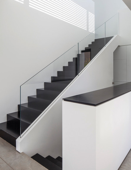 סטודיו לוי חמיצר 06, ג, מדרגות ברזל שחורות, מעקה שקוף, וקרני שמש ה (צילום: עמית גירון)