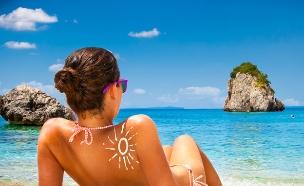 אישה משתזפת על החוף (צילום: Aleksandar Todorovic, Shutterstock)
