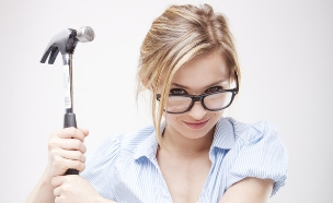 אישה עם פטיש מעל קופת חיסכון (אילוסטרציה: Shutterstock)