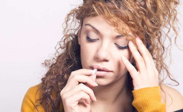 לוקחת כדור נגד כאב ראש (צילום: Shutterstock/javitrapero.com)