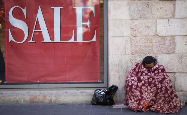 חסר בית מתחמם עם שמיכה בפתח חנות בירושלים (צילום: נתי שוחט, יונתן זינדל, רועי אלימה, פלאש 90)