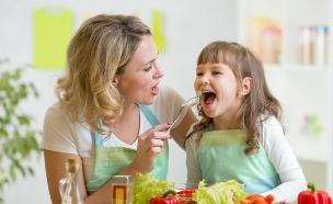 אמא מאכילה ילדה (צילום: Oksana Kuzmina, Shutterstock)