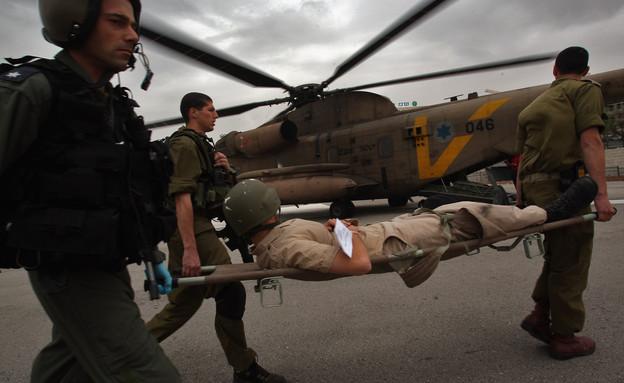 צוות חיילים מחלצים עם אלונקה ברקע מסוק (צילום: David Silverman, GettyImages IL)