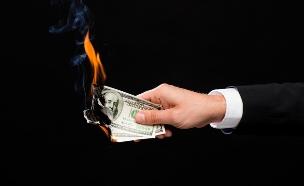 יד מחזיקה שטרות דולר שנשרפים (אילוסטרציה: Shutterstock)