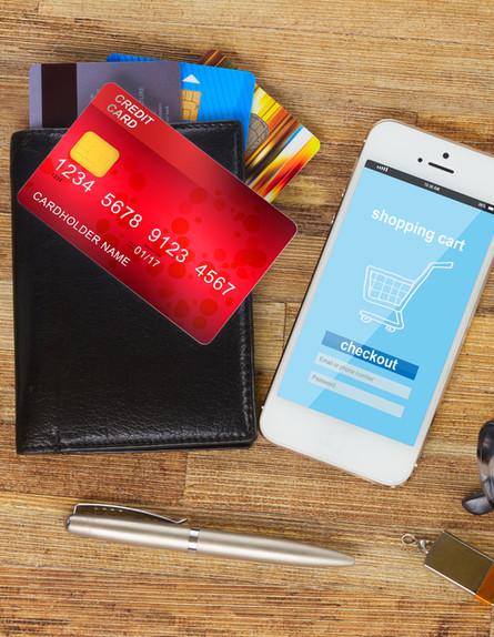 כרטיסי אשראי ליד סמארטפון עם אתר קניות (אילוסטרציה: Neirfy, shutterstock)