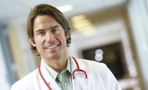רופא צעיר בחלוק ובסטטוסקופ מחייך למצלמה (צילום: jupiter images)