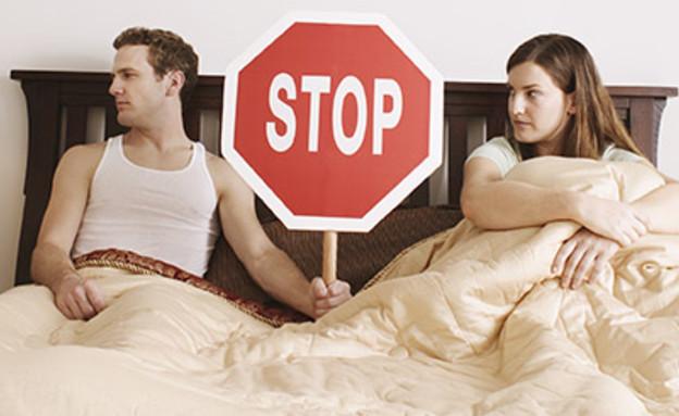 גבר ואישה במיטה הגבר מחזיק תמרור עצור ביניהם (צילום: jupiter images)