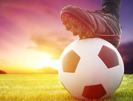 רגל מחזיקה כדורגל על הדשא (צילום: ShutterStock)