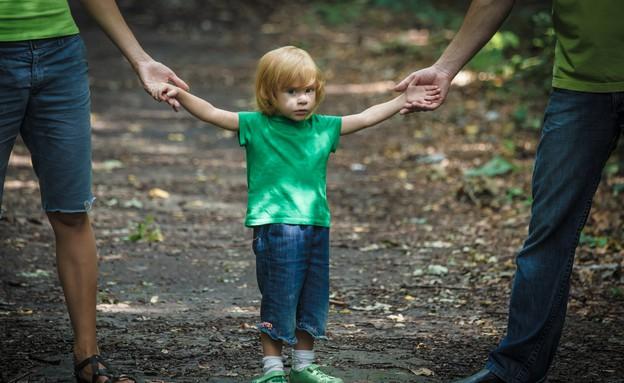 ילד מחזיק בידיים של הוריו (אילוסטרציה: Shutterstock)